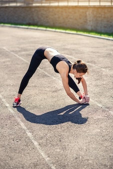 Fitness woman doing stretching on the sadium before training