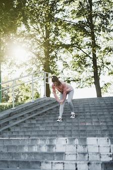 屋外でストレッチトレーニングをしているフィットネス女性。屋外で運動するスポーツウェアの白人女性