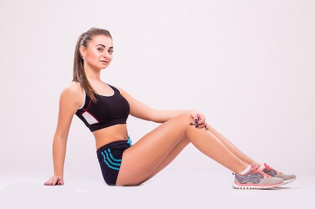 ストレッチトレーニングをしているフィットネス女性。白い背景で隔離の若い女性の全身ショット。