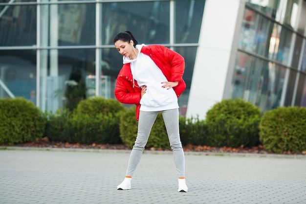 モダンな建物の背景に立ってトレーニングをしているフィットネス女性。