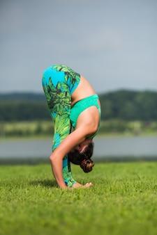 Donna di forma fisica che fa esercizio di yoga e rilassarsi con abbigliamento sportivo nel parco verde in estate
