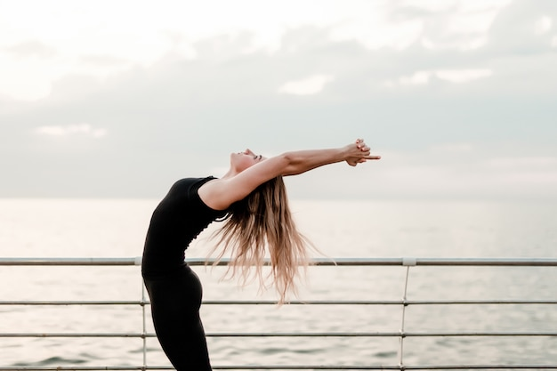 Fitness woman doing yoga and exercising asana near the sea on sunrise