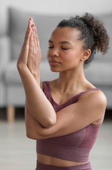 Donna di forma fisica che fa yoga a casa