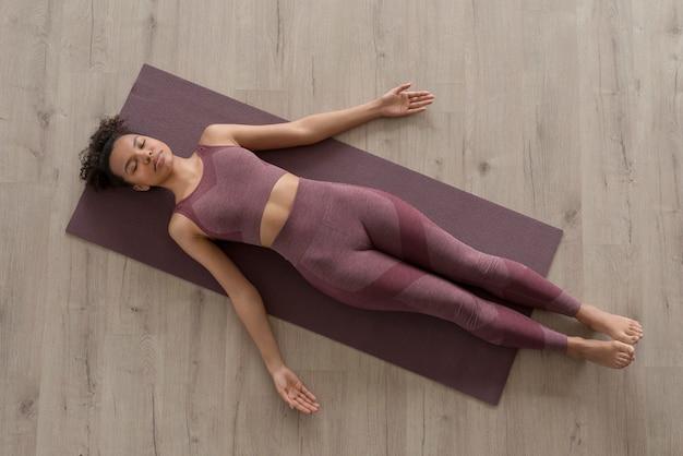 Женщина фитнеса занимается йогой на коврике для йоги дома