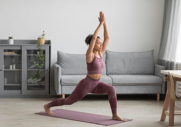 Fitness woman doing yoga on a yoga mat at home
