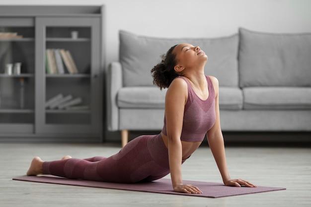 Donna di forma fisica che fa yoga su una stuoia di yoga a casa