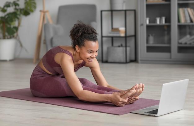 Donna di forma fisica che fa yoga su una stuoia di yoga a casa Foto Gratuite