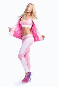 Fitness woman dressed in pink sportswear isolated on white background