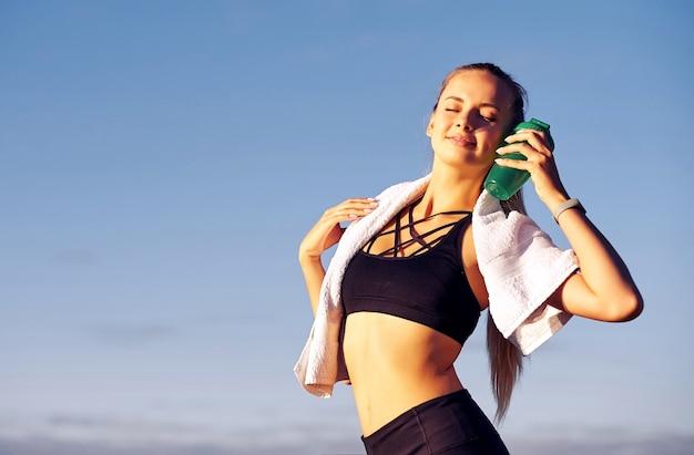 푸른 하늘 배경에서 훈련을 한 후 물을 마시는 피트니스 여성
