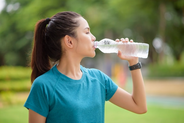 Fitness woman drinking water after workout in park