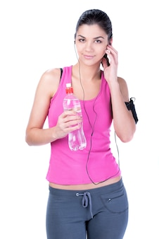 Fitness woman drinking water and listening to music.