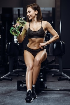 Fitness woman drinking water at workout in the gym