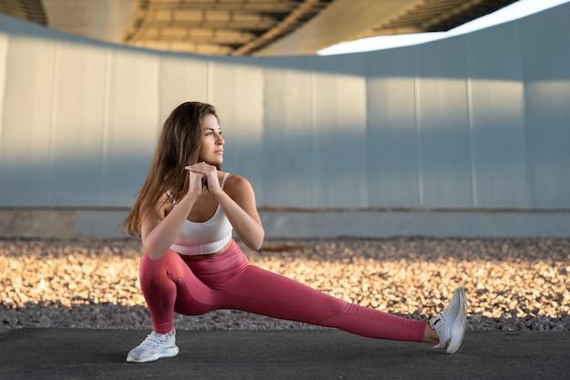 フィットネス女性は屋外で朝の運動を楽しむ