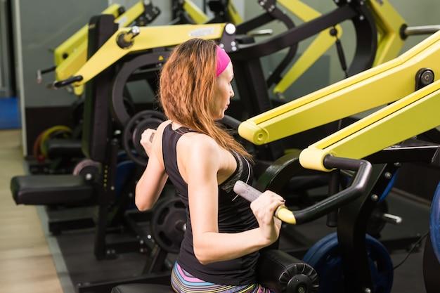 Фитнес-женщина выполняет упражнения с тренажером в тренажерном зале