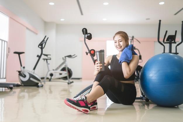 フィットネス女性は、ジムで運動し、ボトルから水を飲む。