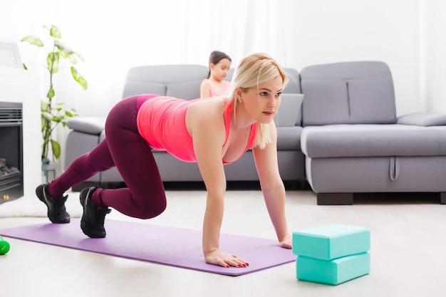 自宅の床で運動するフィットネス女性