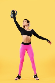 Fitness woman in fashionable pink and black sportswear work out with kettlebell on yellow wall. strength and motivation.