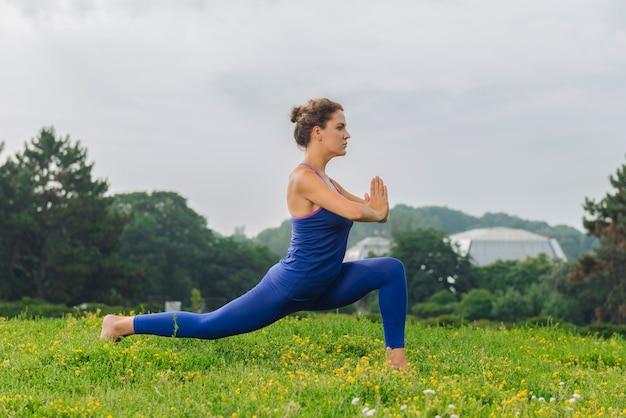 Женщина фитнеса чувствует гармонию, балансируя и растягиваясь на выходных на открытом воздухе