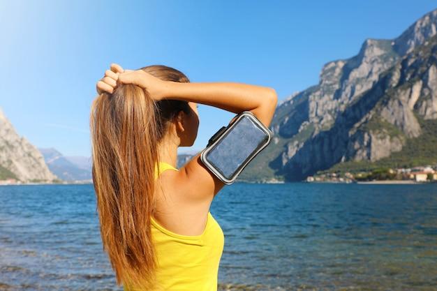 フィットネス女性が彼女の毎日のトレーニングで屋外の髪を修正する彼女は、スマートフォンのスポーツアームバンドを使用しています。
