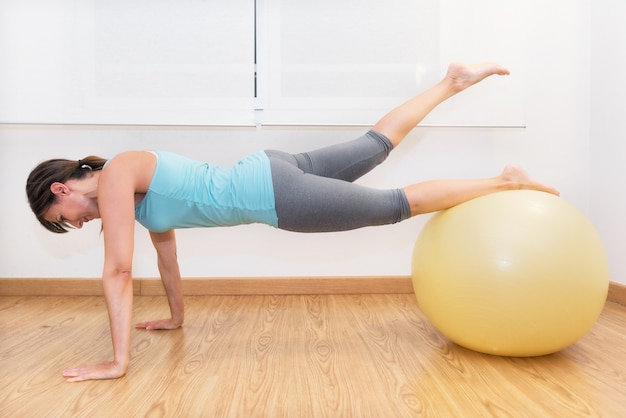 Fitness woman in gym on pilates ball. young woman doing exercise on fitness ball.