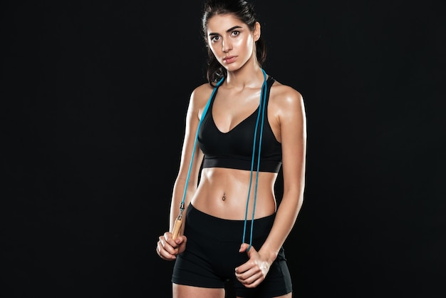 Fitness woman in gym standing over black wall and make sport exercises holding jumping rope