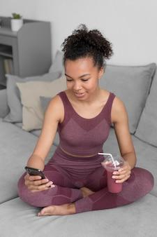 スマートフォンを使用しながらデトックスジュースを持っているフィットネス女性
