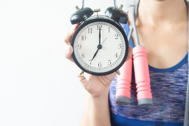 Fitness woman holding alarm clock,