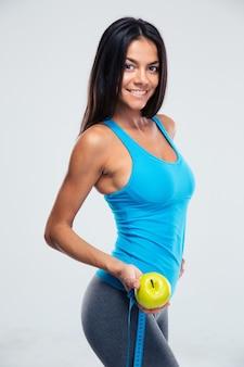 Женщина фитнеса, держащая яблоко и измерительная лента