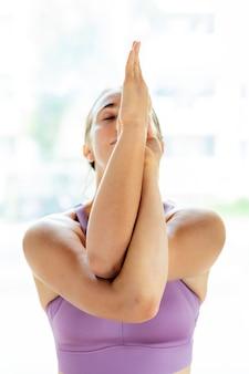 Женщина фитнеса в позе гарудасаны