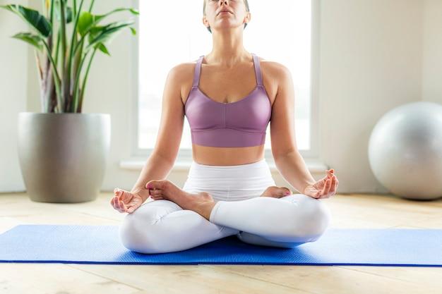 Фитнес-женщина в позе сукхасаны