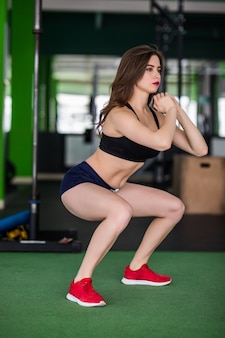 체육관에서 피트 니스 여자는 그녀의 몸을 더 강하게하기 위해 다른 운동을하고있다