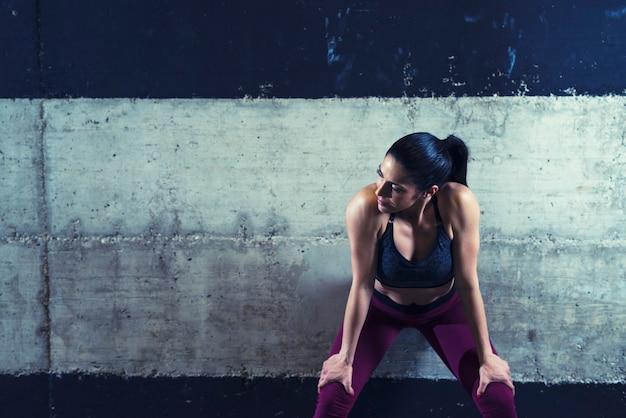 コンクリートの壁に寄りかかって脇を見てスポーツ服を着たフィットネス女性