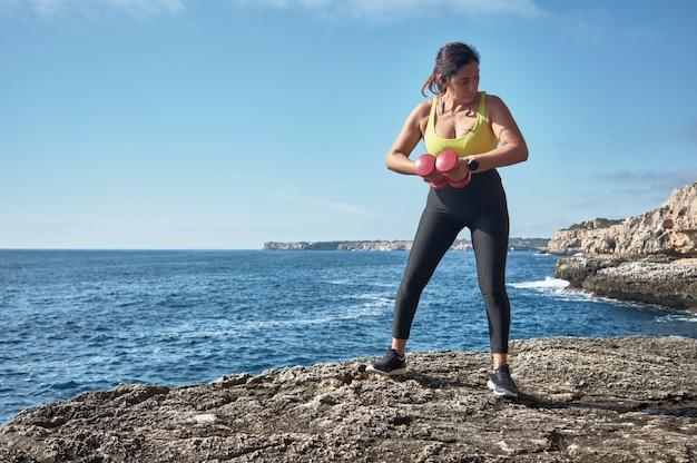 스포츠 피트니스 여성은 물 앞에서 탄성 밴드, 무게, 체육관 운동으로 훈련을 시작합니다.
