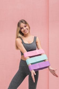 Женщина фитнеса в спортивной одежде демонстрирует руки с резинкой гимнастического эспандера на розовом фоне.