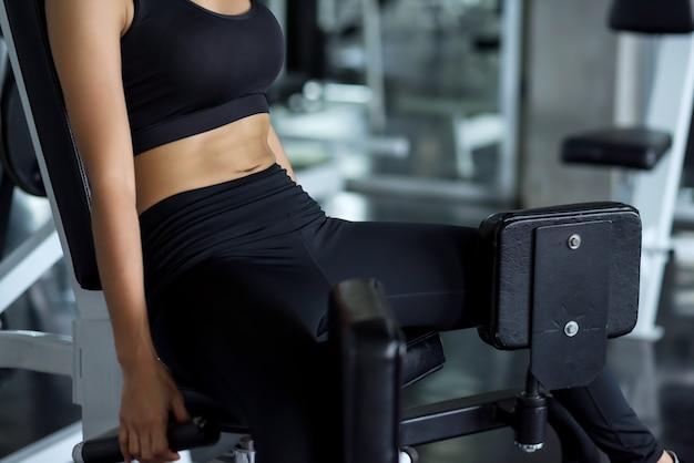 체육관에서 기구 기계와 운동복 운동 다리와 몸통 복근 근육에 피트 니스 여자