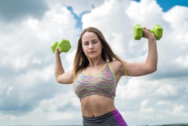 屋外でダンベルを使って運動するスポーツウェアのフィットネス女性