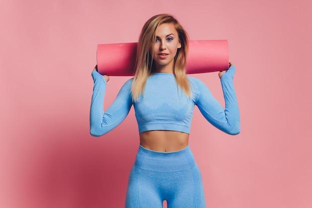 Женщина фитнеса в спортивной одежде на розовом фоне. подходящая и здоровая женщина.