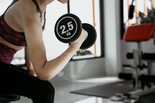 トレーニングのフィットネス女性。午前中に強い腹筋を示します。ジムで