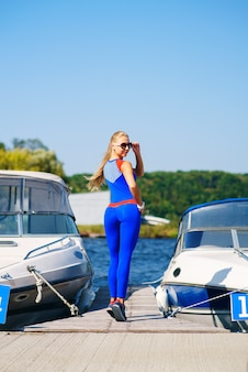 Fitness woman is on the dock in a blue suit among yachts