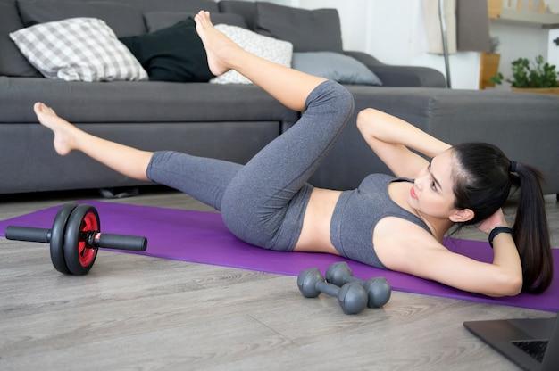 フィットネス女性はマット、健康的なライフスタイル、スポーツコンセプトでクランチを行使して腹筋運動をしています。