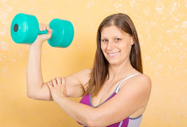 Fitness woman is doing weights for arms at home