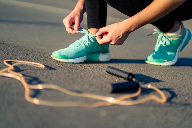 Фитнес женщина связывает шнурки на кроссовках и готовится делать кардио упражнения со скакалкой на открытом воздухе