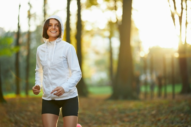 Donna fitness in giacca con cappuccio che si allena all'aperto