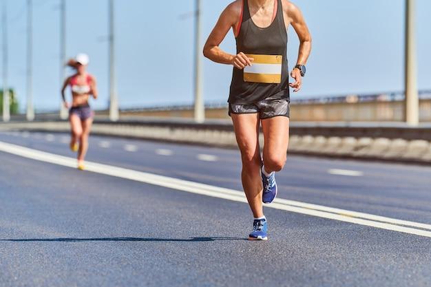 Фитнес женщина, бег в спортивной одежде на городской дороге