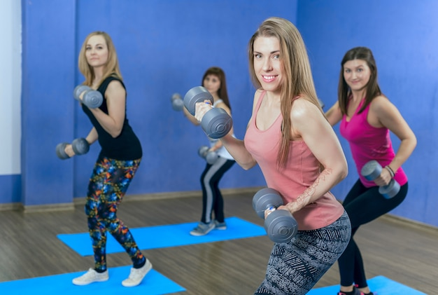 Fitness woman lift dumbbells. train your biceps in gym class in the group