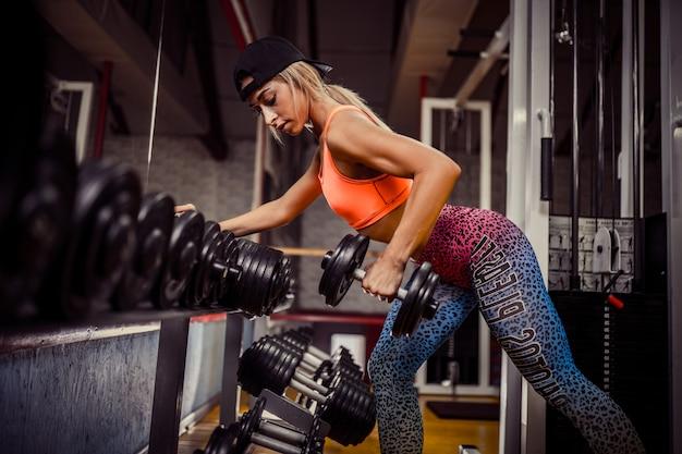 Гантель женщины фитнеса поднимаясь в спортзале. спорт, концепция мотивации.