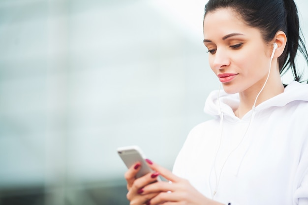Fitness. woman listening music on phone while exercising outdoors - sport and healthy lifestyle concept