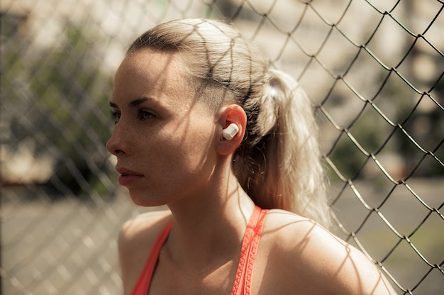 Fitness woman listening music in wireless headphones, doing workout exercises on street