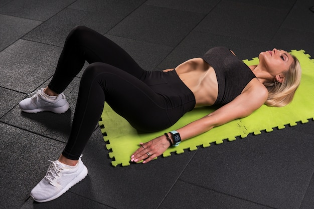 Fitness woman lying and doing vacuum exercise in gym