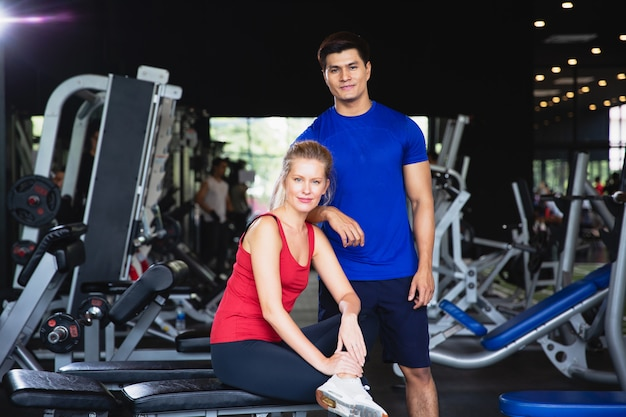 Fitness woman and man with sportswear sitting and look at camera after exercise at gym sport with copy space, healthy couple workout bodybuilding, yoga and fitness work out healthcare concept